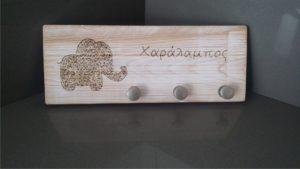 ελεφαντάκι παιδική κρεμμάστρα τοίχου με όνομα παιδιού - handicraftcyprus.com - όλα τα είδη χειροτεχνημάτων του εργαστηρίου μας. χειροποίητα δώρα, τάβλια με σκάλισμα και πυρογραφία, σκάκια σκαλιστά, ξύλινα ρολόγια με σκάλισμα, παιδικά κρεμμασταράκια με παιδικούς ήρωες, ξύλινες φιγούρες και σχήματα, σχέδιο με πυρογράφο σε νεροκολοκύθες, μπομπονιέρες βάφτισης, μπομπονιέρες γάμου γάμων, επιχειρηματικά δώρα, ξεχωριστά δώρα επιχειρήσεων, παλαίωση φωτογραφίας, μπαούλα σκαλιστά, κρεμμασταράκια τοίχου για κλειδιά, κρεμμαστάρια ρούχων σκαλιστά, σκαλιστές κορνίζες, χειροποίητοι καθρέφτες με σκάλισμα, εικόνες αγίων με σκάλισμα, παλαιωμένες εικόνες αγίων, διακοσμητικά είδη χειροποίητα, αξεσουάρ γραφείου, σχέδια σε ξύλο, ξυλογλυπτική, παλαίωση εικόνων, αγιογραφίες, πυρογραφία, χαλκογραφία, κορνίζες, καθρέφτες, χειροποίητα, βάφτιση, γάμος, επέτειος, Πάφος, Λευκωσία, Λεμεσός, Λάρνακα.
