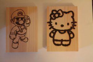 hello kitty και σούπερ μάριο σχέδιο με πυρογραφία - ξύλινες φιγούρες και σχέδια - handicraftcyprus.com - όλα τα είδη χειροτεχνημάτων του εργαστηρίου μας. χειροποίητα δώρα, τάβλια με σκάλισμα και πυρογραφία, σκάκια σκαλιστά, ξύλινα ρολόγια με σκάλισμα, παιδικά κρεμμασταράκια με παιδικούς ήρωες, ξύλινες φιγούρες και σχήματα, σχέδιο με πυρογράφο σε νεροκολοκύθες, μπομπονιέρες βάφτισης, μπομπονιέρες γάμου γάμων, επιχειρηματικά δώρα, ξεχωριστά δώρα επιχειρήσεων, παλαίωση φωτογραφίας, μπαούλα σκαλιστά, κρεμμασταράκια τοίχου για κλειδιά, κρεμμαστάρια ρούχων σκαλιστά, σκαλιστές κορνίζες, χειροποίητοι καθρέφτες με σκάλισμα, εικόνες αγίων με σκάλισμα, παλαιωμένες εικόνες αγίων, διακοσμητικά είδη χειροποίητα, αξεσουάρ γραφείου, σχέδια σε ξύλο, ξυλογλυπτική, παλαίωση εικόνων, αγιογραφίες, πυρογραφία, χαλκογραφία, κορνίζες, καθρέφτες, χειροποίητα, βάφτιση, γάμος, επέτειος, Πάφος, Λευκωσία, Λεμεσός, Λάρνακα.